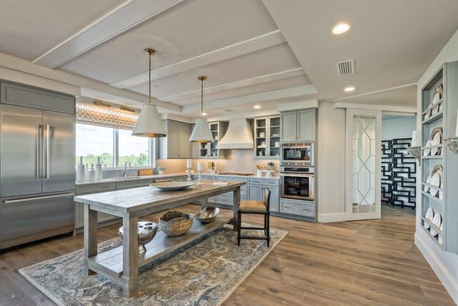 The kitchen in the furnished Seaglass tower residence 306 model presents a clean aura with light countertops and island that play against warm wood toned flooring.