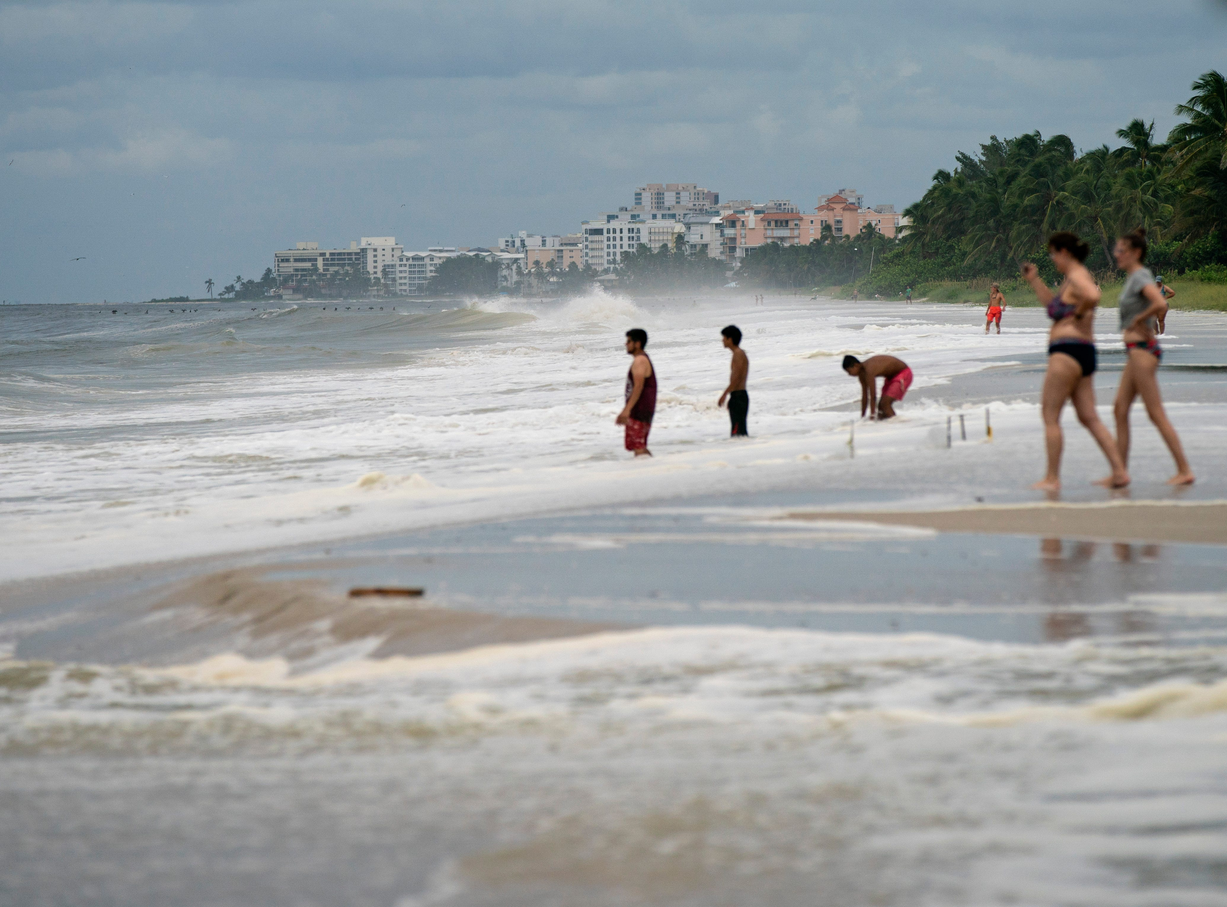 Beachgoers walk near the Naples Pier as Hurricane Michael's wind pushes the waves close to the dunes in Naples, FL. Tuesday, Oct. 9, 2018.