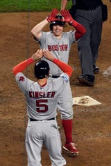 Boston Red Sox's Ian Kinsler (5) and Brock Holt celebrate Holt's two-run homerun in the ninth inning, making him the first player in postseason history to hit for the cycle, in Game 3 of the American League Division Series on Monday, Oct. 8, 2018, in New York.
