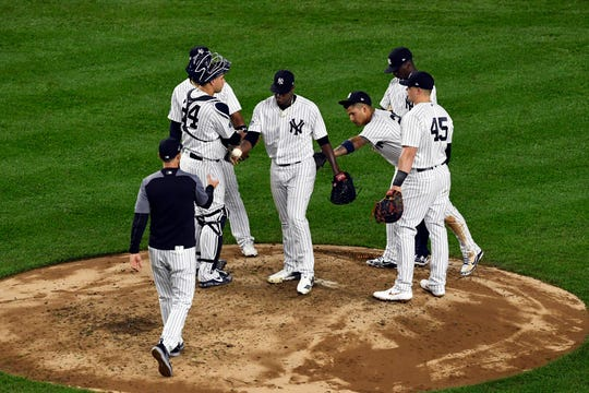 New York Yankees pitcher Luis Severino, center, hands the ball to manager Aaron Boone as he leaves the mound in the fourth inning in Game 3 of the American League Division Series on Monday, Oct. 8, 2018, in New York.
