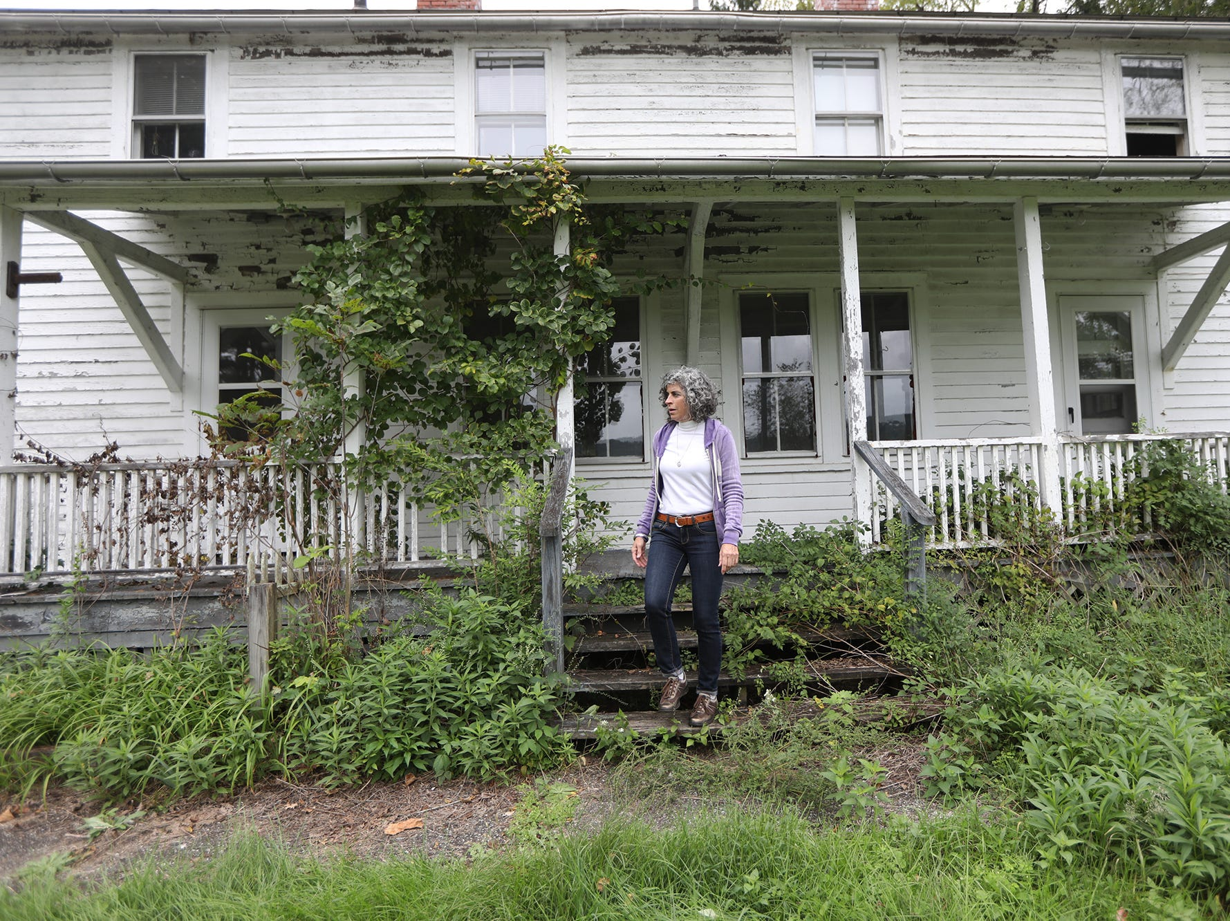 Rosemarie Briegel, 62, currently of Sandyston, is shown in front of the Walpack home where she lived for the majority of her first 20 years. Sunday, September 23, 2018