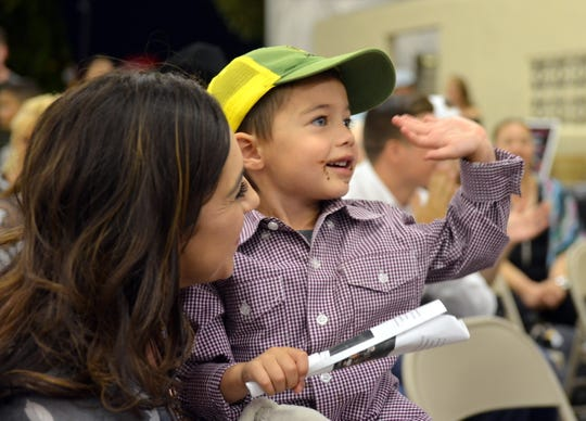 Cayden Viramontes, 3, helps his mom, Jaime Viramontes place bids during the Cake Auction.