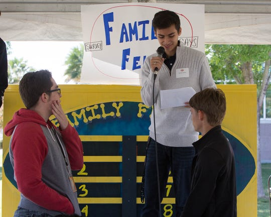 """Mathew Madrid, the Associated Students of New Mexico State University Assistant Director of Governmental Affairs, asks a question about the county's original colonies to """"Family Feud"""" contestants Caleb Estep, 18, left, from Centennial High School, and Jay Choate, 17, from Oñate High School on Tuesday Oct. 9, 2018. About 300 seniors from area high schools came to a Celebrating Democracy event at the Doña Ana County Government Center."""