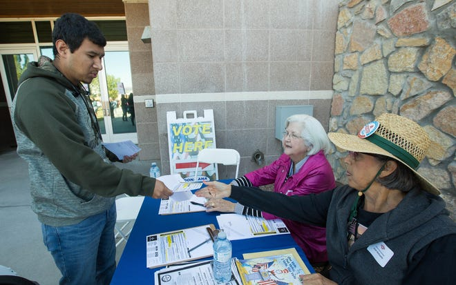 Alberto Hernandez, 18, a Mayfield High School Senior hands his voter registration card to Jean Berlowitz and Pat Warner during the Celebrating Democracy in Doña Ana County event at the Doña Ana County Government Center Tuesday, Oct. 9, 2018.