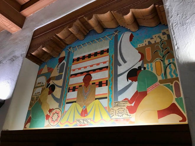 A Great Depression-era mural that depicts Native Americans is seen on the wall of the west wing at the University of New Mexico's Zimmerman Library in Albuquerque, N.M., on Monday, Oct. 8, 2018. The mural is among a series of paintings that would be covered amid complaints.