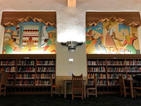 Two Great Depression-era murals that depict Native Americans and Hispanics are seen on the walls of the west wing at the University of New Mexico's Zimmerman Library on Monday, Oct. 8, 2018. The murals are among a series of paintings that would be covered amid complaints.