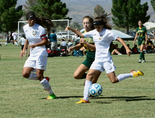 Alamogordo Lady Tiger Janae Shaklee (2) is about to send the ball towards the goal. Her attempt would be blocked, however, Shawna Williams (13), left, would later succeed in putting the Lady Tigers on the scoreboard at the 68th minute at their game Saturday against the Mayfield Lady Trojans.