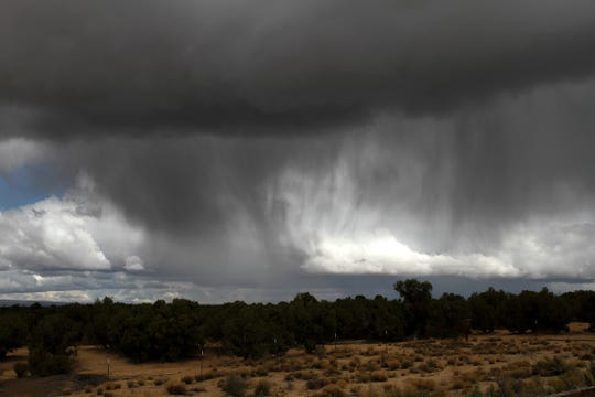 Rain sweeps across an area north of the Hood Mesa Trail Tuesday north of Farmington.