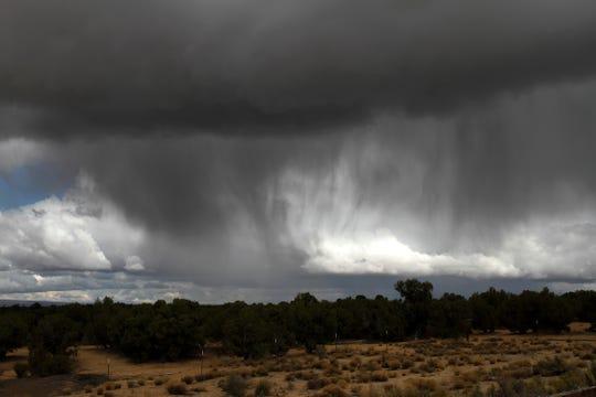 Rain sweeps across an area north of the Hood Mesa Trail Tuesday north of Farmington.