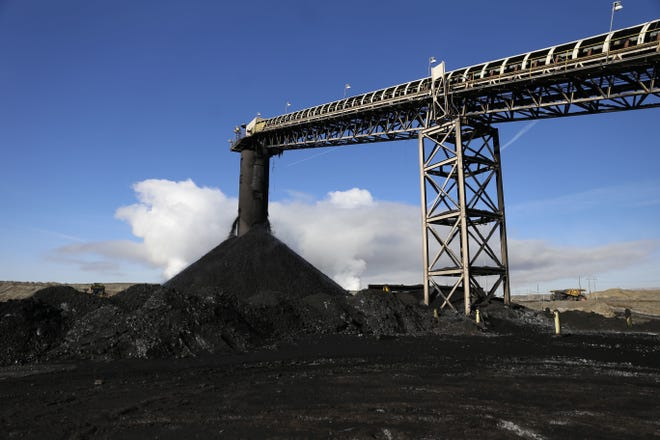 Coal pours from a conveyor belt in a file photo from January 2016 at the San Juan Mine in Waterflow.