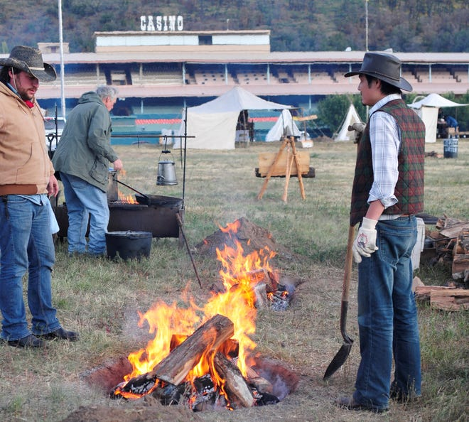 In this file photo, two cowboys tend to their fire in preparation for the 2011 Cowboy Symposium Chuck Wagon Cookoff at Ruidoso Downs.