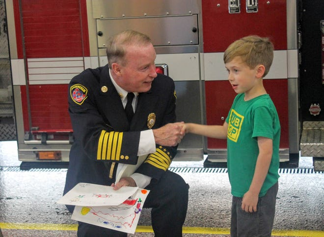 Birmingham Fire Chief John Connaughton shakes hands with Kingston Hansen, 7 of Birmingham, after Hansen presented him some pictures he drew.