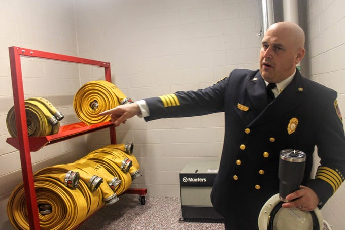 Assistant Fire Chief Paul Wells points to new racks holding the department's hoses in the new fire station.