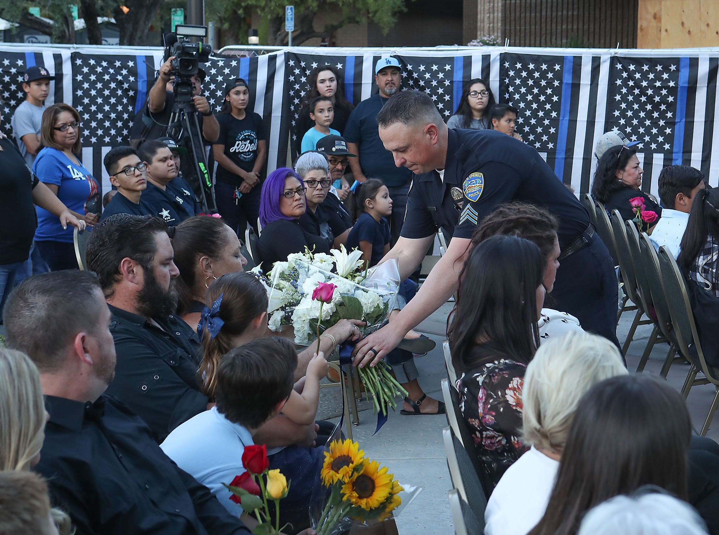 "Flowers are presented to the families of Jose ""Gil"" Vega and Lesley Zerebny during a vigil at the Palm Springs Police Department commemorating the two-year anniversary of their passing, October 8, 2018."