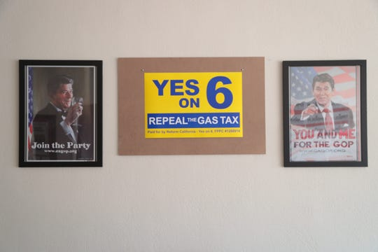 """Posters for the California GOP hang next to a """"repeal the gas tax"""" sign in the Cathedral City office of Kimberlin Brown Pelzer, August 22, 2018."""