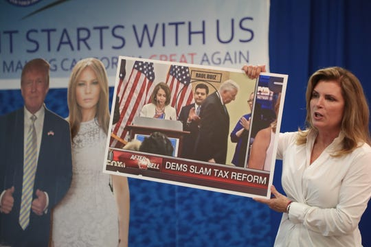 Kimberlin Brown Pelzer holds up a poster criticizing Congressman Raul Ruiz's position on tax reform at an event held at the East Valley Republican Women Headquarters in La Quinta, Calif., August 22, 2018.