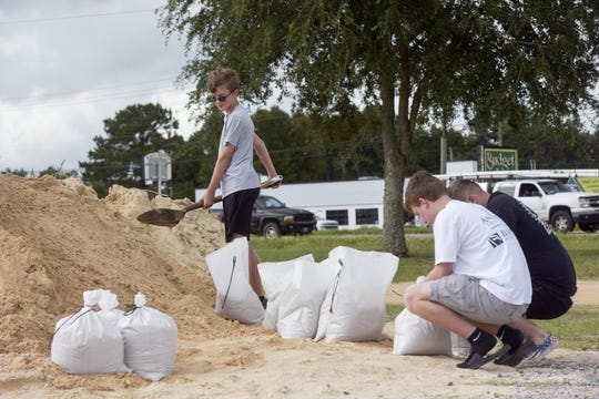 The Harberson family in Cantonment takes advantage of the free sand provided by the county to fill sand bags in preparation for Hurricane Michael.