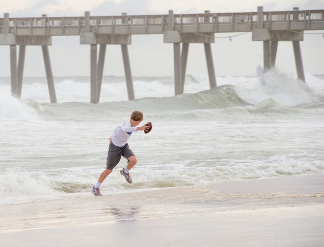Chase Herring runs away from an incoming wave after cleaning off his football at Casino Beach in Pensacola as Hurricane Michael approaches the Florida panhandle on Tuesday, October 9, 2018.