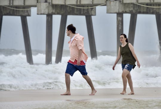 Spectators walk along the beach as red flags fly over Pensacola Beach on Tuesday, Oct. 9, 2018, as Hurricane Micheal churns in the Gulf.