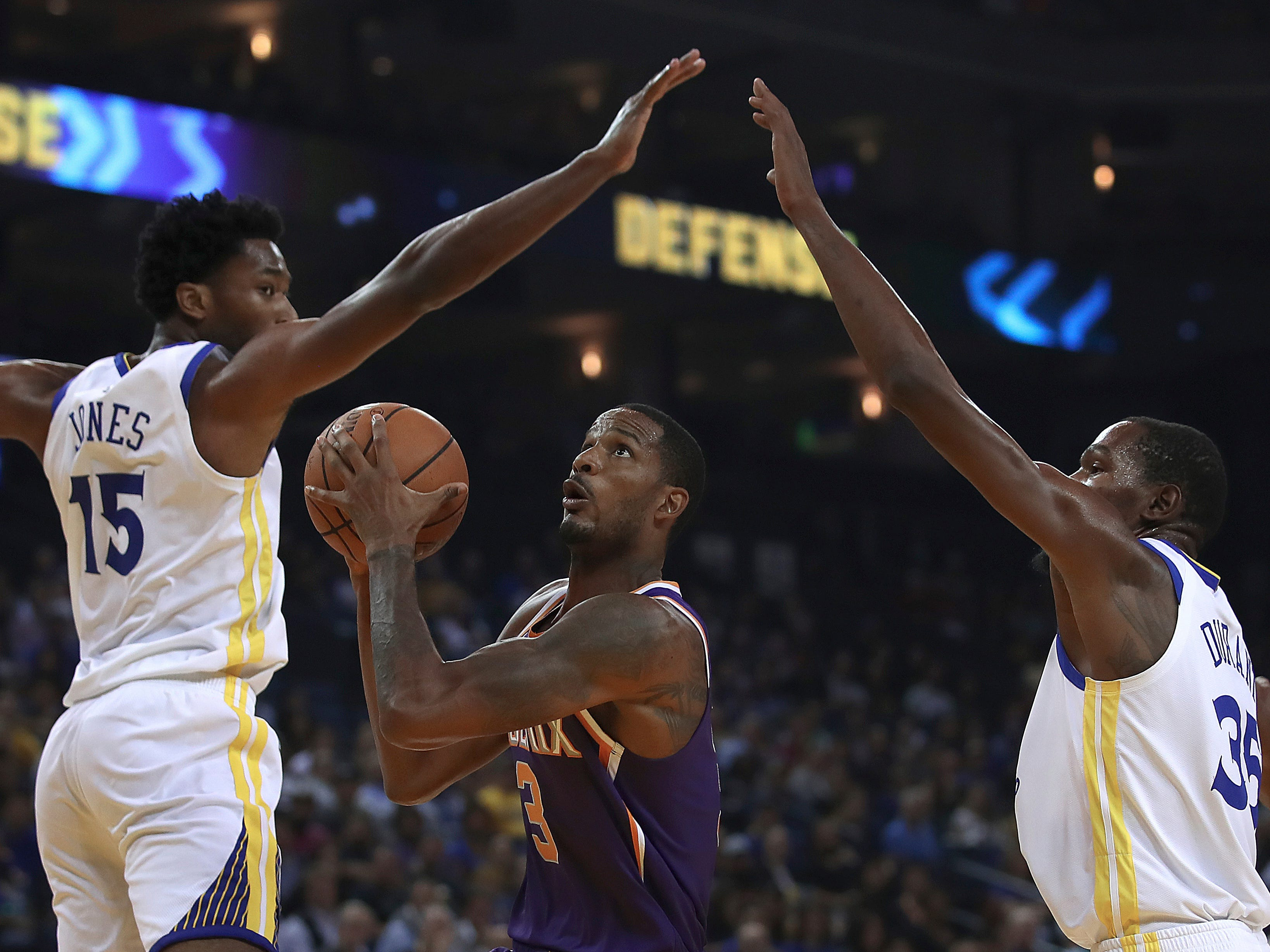 Phoenix Suns' Trevor Ariza, center, looks to shoot between Golden State Warriors' Damian Jones (15) and Kevin Durant, right, during the first half of a preseason NBA basketball game Monday, Oct. 8, 2018, in Oakland, Calif.