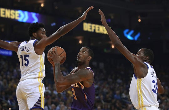 Phoenix Suns' Trevor Ariza, center, looks to shoot between Golden State Warriors' Damian Jones (15) and Kevin Durant, right, during the first half of a preseason NBA basketball game Monday, Oct. 8, 2018, in Oakland, Calif. (AP Photo/Ben Margot)