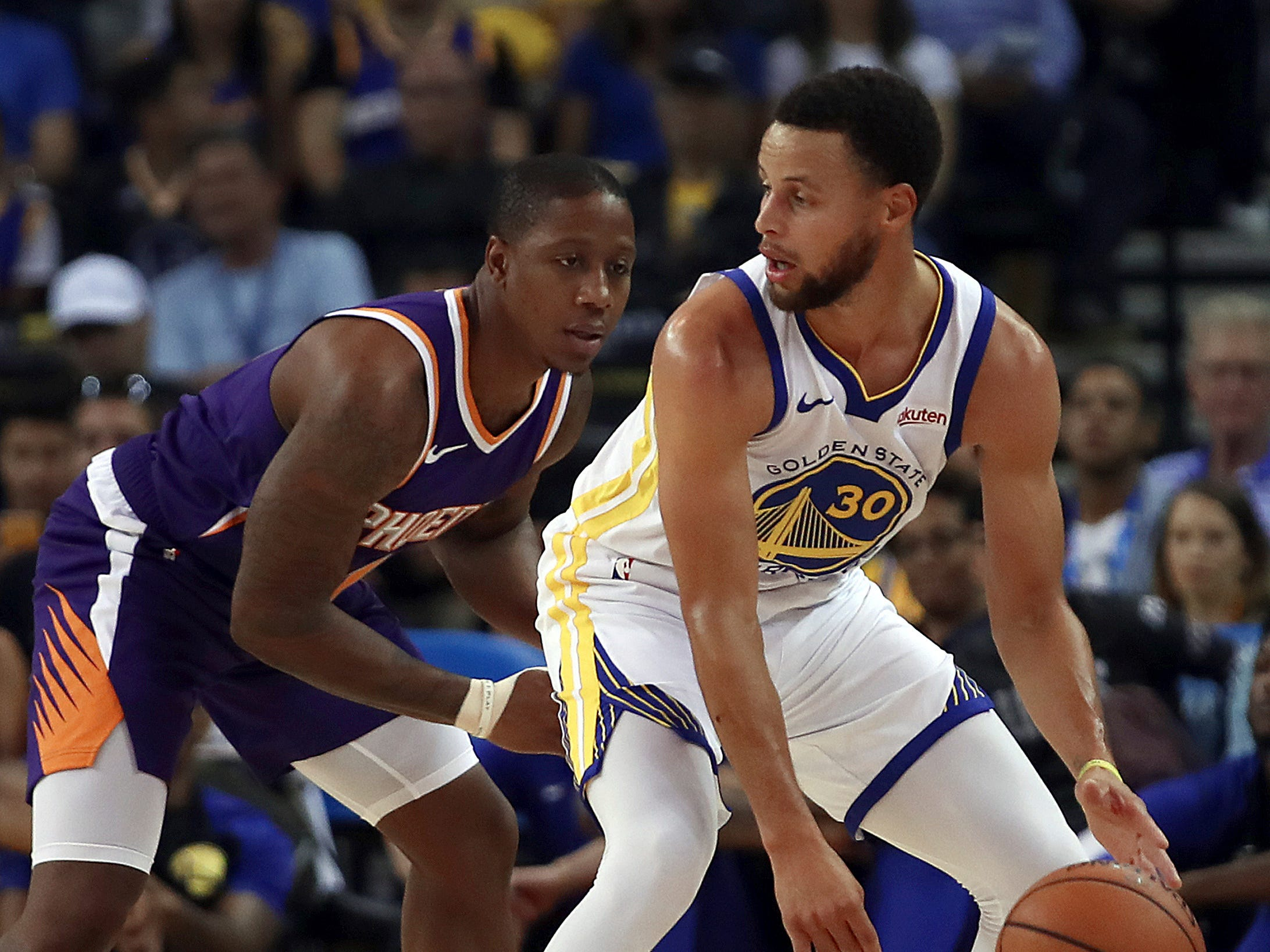 Phoenix Suns' Isaiah Canaan, left, guards Golden State Warriors' Stephen Curry (30) during the first half of a preseason NBA basketball game Monday, Oct. 8, 2018, in Oakland, Calif.