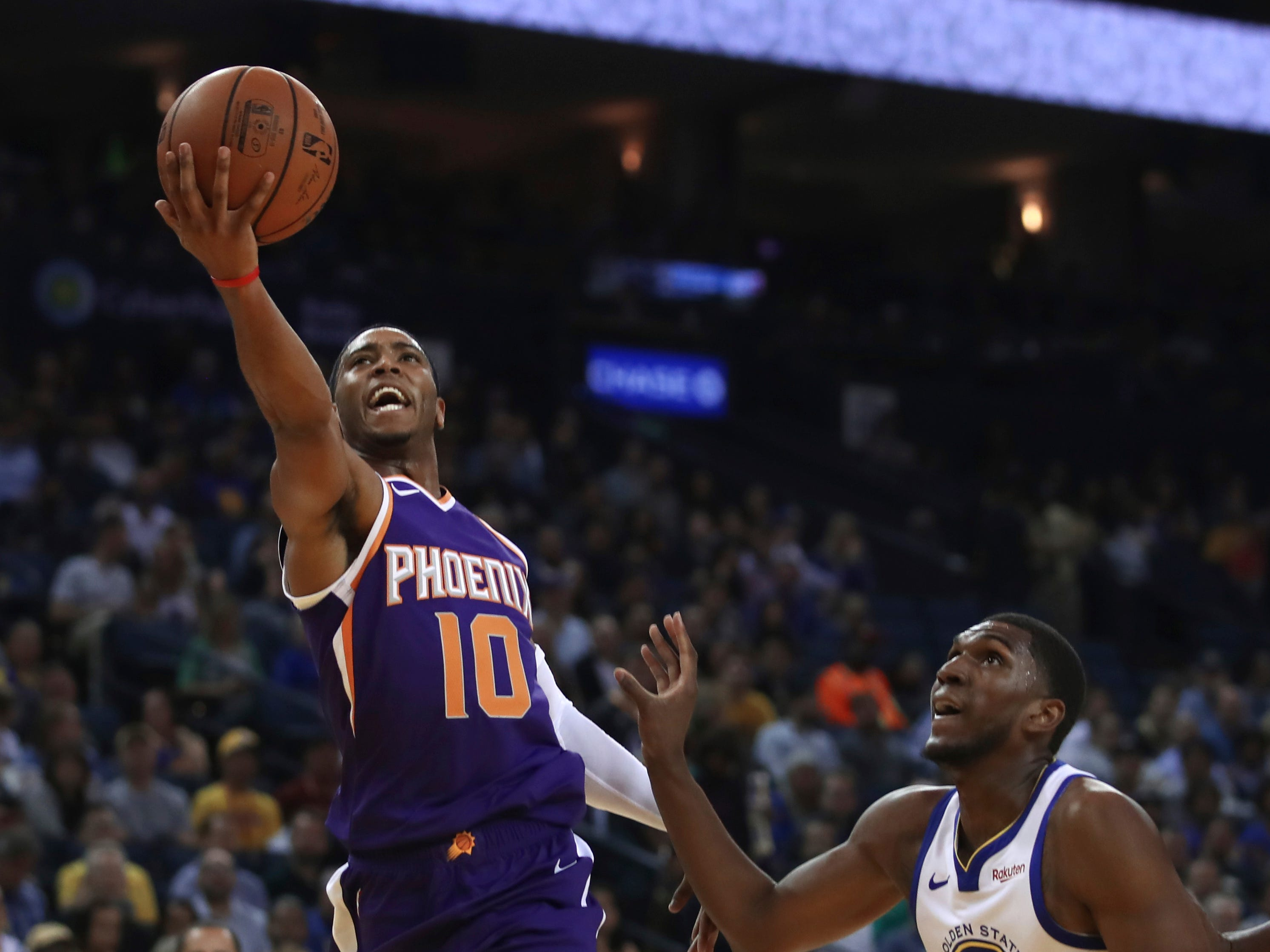 Phoenix Suns' Shaquille Harrison, left, lays up a shot past Golden State Warriors' Kevon Looney (5) during the first half of a preseason NBA basketball game Monday, Oct. 8, 2018, in Oakland, Calif.