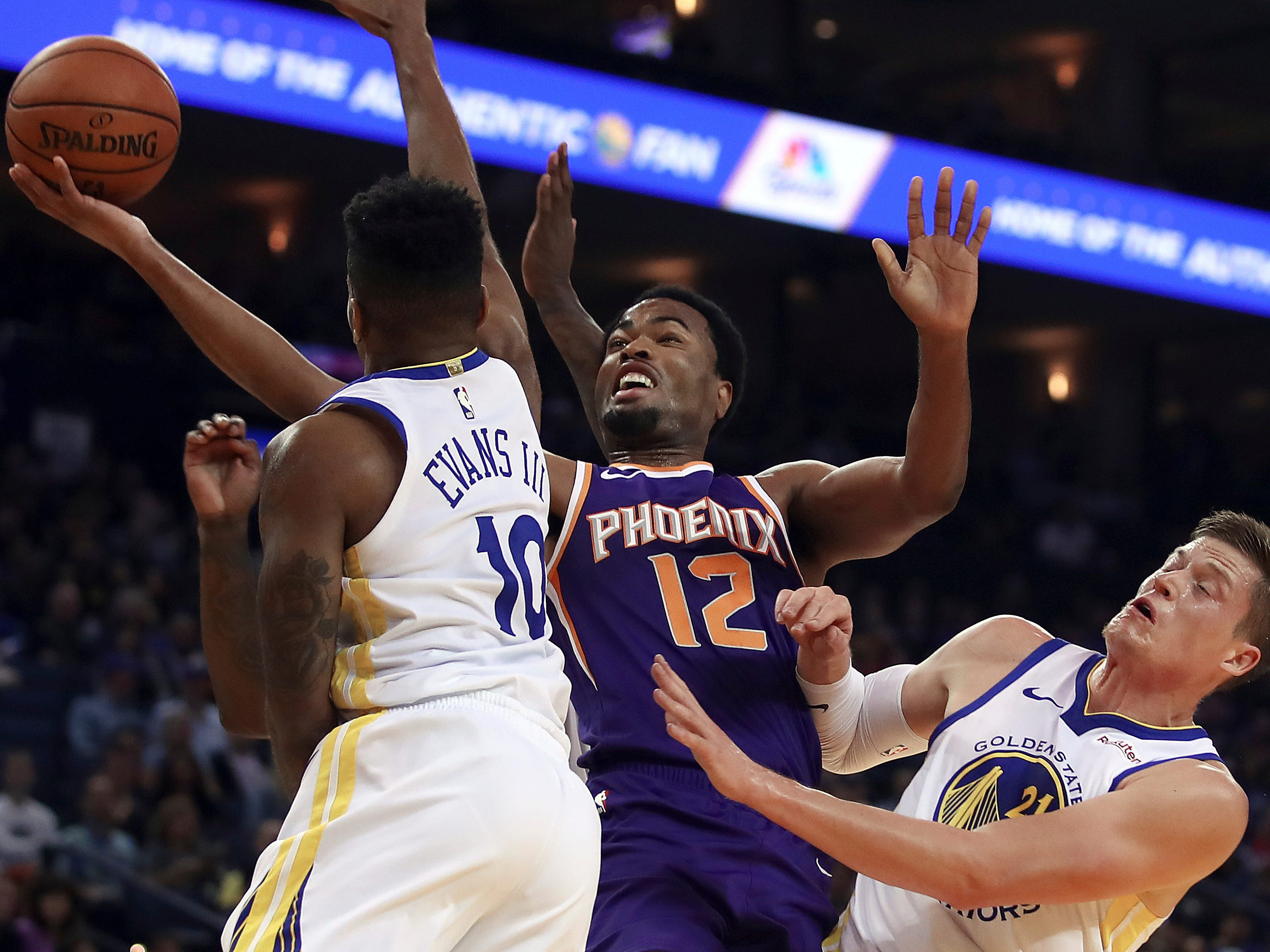 Phoenix Suns' TJ Warren (12) lays up a shot between Golden State Warriors' Jacob Evans, left, and Jonas Jerebko (21) during the first half of a preseason NBA basketball game Monday, Oct. 8, 2018, in Oakland, Calif.