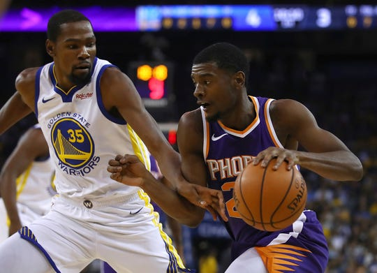 Phoenix Suns' Josh Jackson, right, drives the ball against Golden State Warriors' Kevin Durant (35) during the first half of a preseason NBA basketball game Monday, Oct. 8, 2018, in Oakland, Calif.