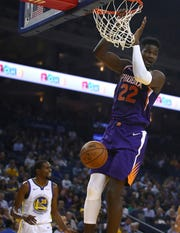 Phoenix Suns' Deandre Ayton (22) scores against the Golden State Warriors during the first half of a preseason NBA basketball game Monday, Oct. 8, 2018, in Oakland, Calif. (AP Photo/Ben Margot)