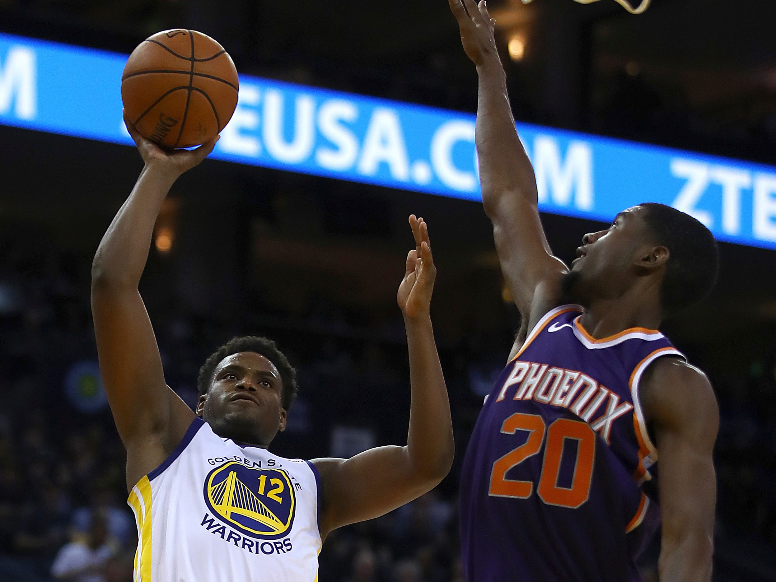 Golden State Warriors' Danuel House Jr., left, lays up a shot against Phoenix Suns' Josh Jackson (20) during the second half of a preseason NBA basketball game Monday, Oct. 8, 2018, in Oakland, Calif.