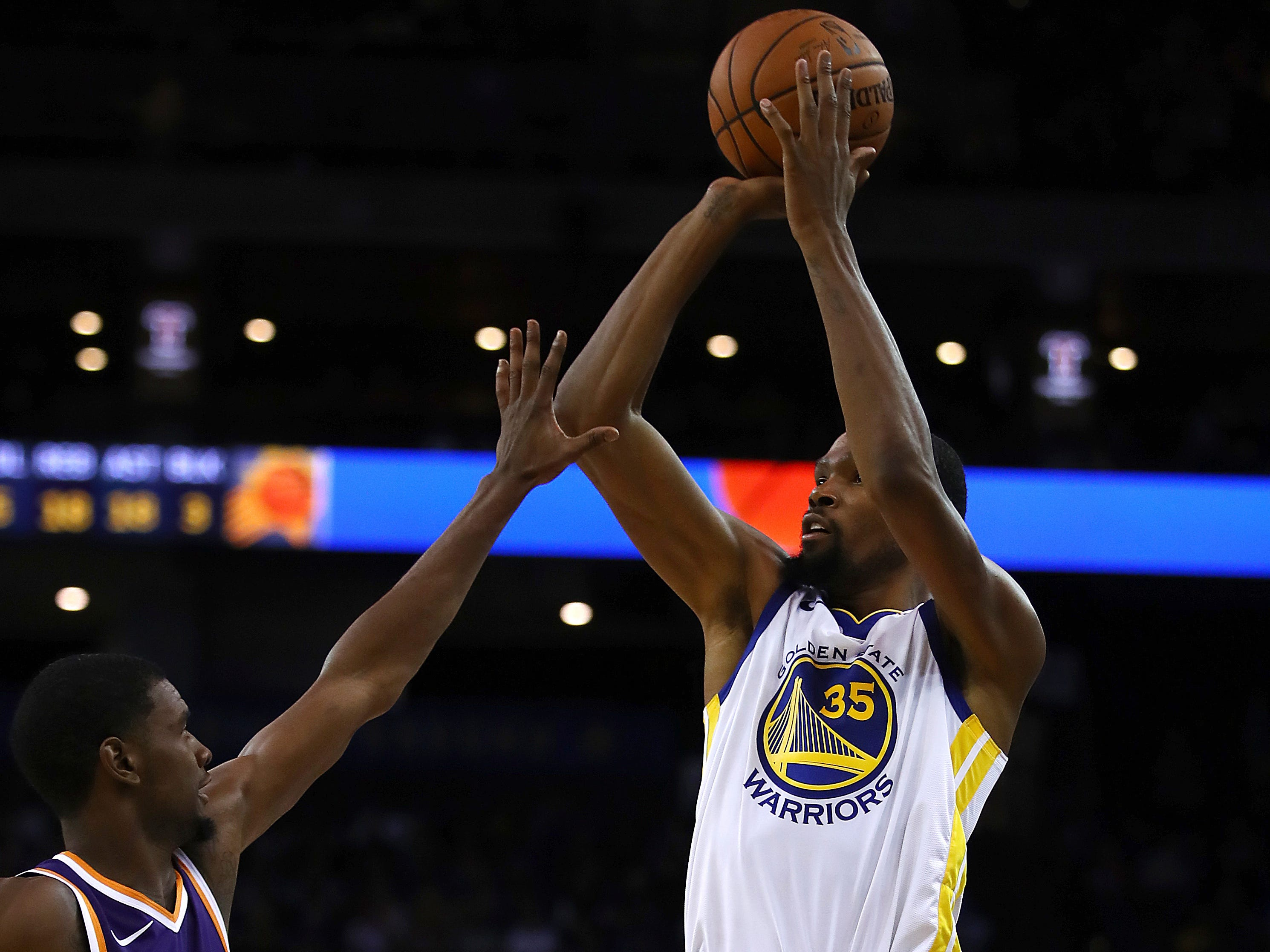Golden State Warriors' Kevin Durant, right, shoots over Phoenix Suns' Josh Jackson (20) during the second half of a preseason NBA basketball game Monday, Oct. 8, 2018, in Oakland, Calif.