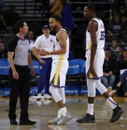 Golden State Warriors' Stephen Curry, center, and Kevin Durant (35) speak with referee Ben Taylor during the second half of a preseason NBA basketball game against the Phoenix Suns Monday, Oct. 8, 2018, in Oakland, Calif.