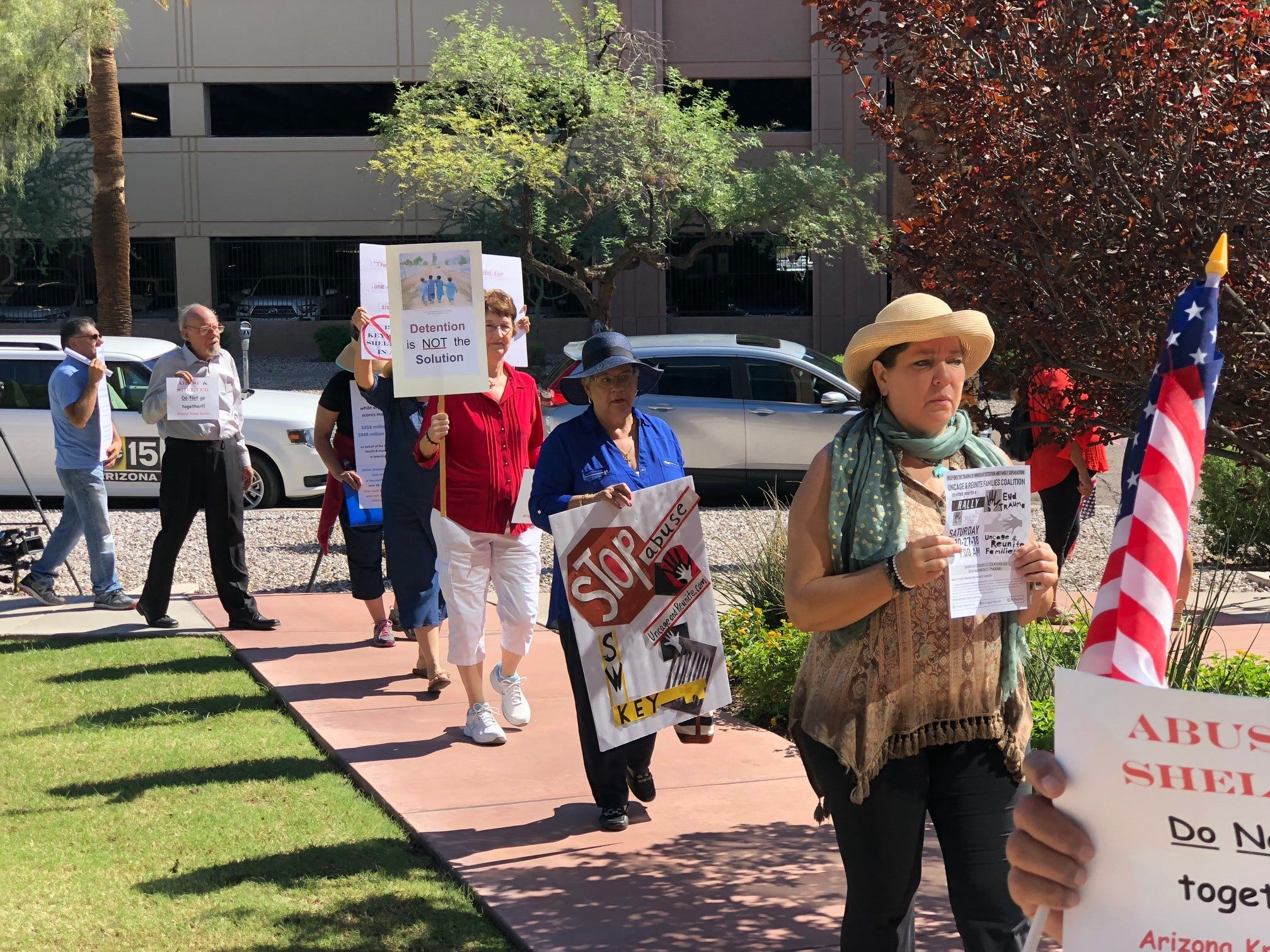 The Uncage & Reunite Families Coalition protests Tuesday morning in front of the Arizona Department of Health Services building.