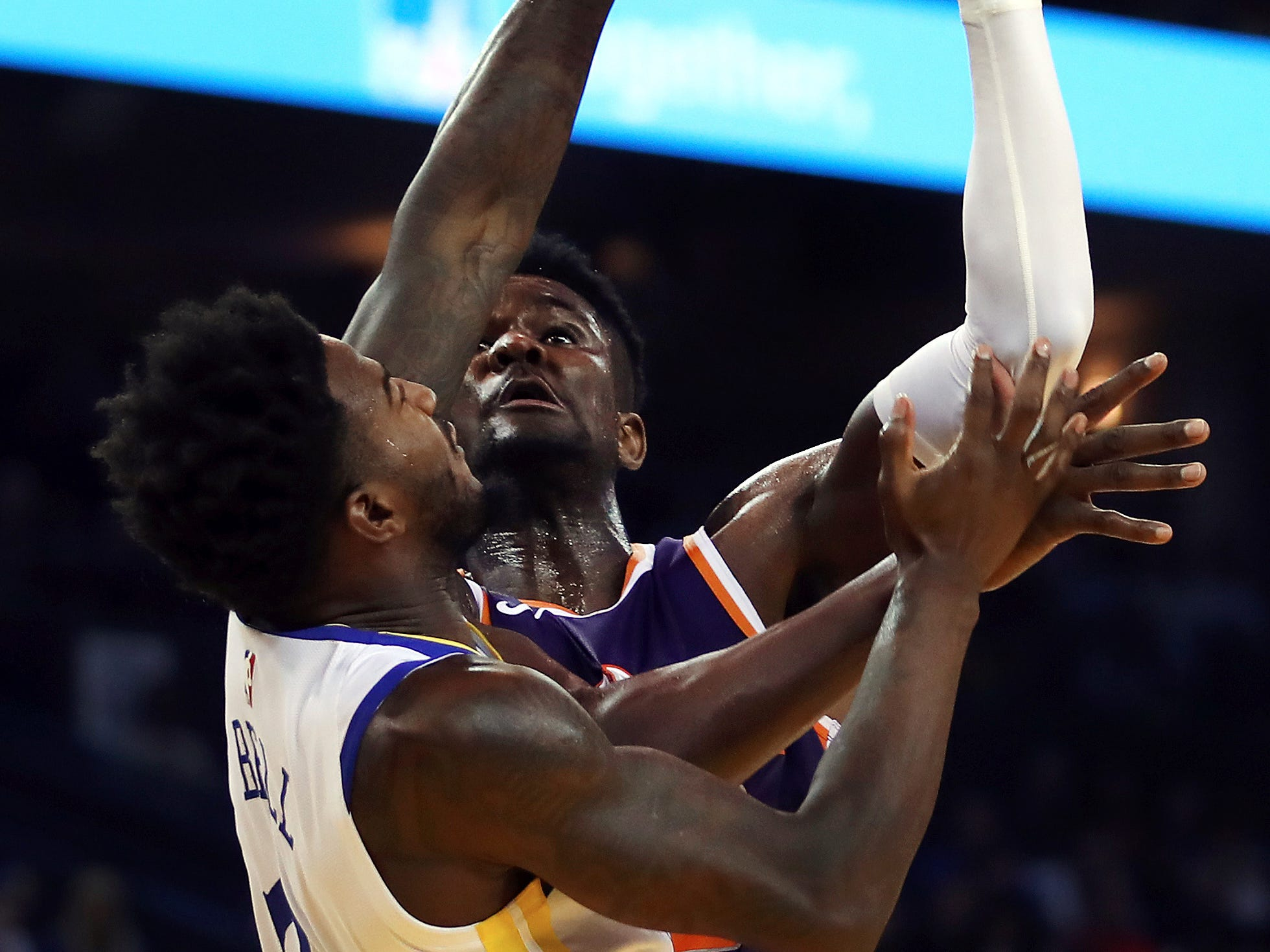 Phoenix Suns' Deandre Ayton shoots over Golden State Warriors' Jordan Bell, left, during the first half of a preseason NBA basketball game Monday, Oct. 8, 2018, in Oakland, Calif.