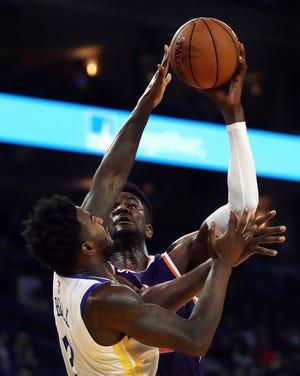 Phoenix Suns' Deandre Ayton shoots over Golden State Warriors' Jordan Bell, left, during the first half of a preseason NBA basketball game Monday, Oct. 8, 2018, in Oakland, Calif.