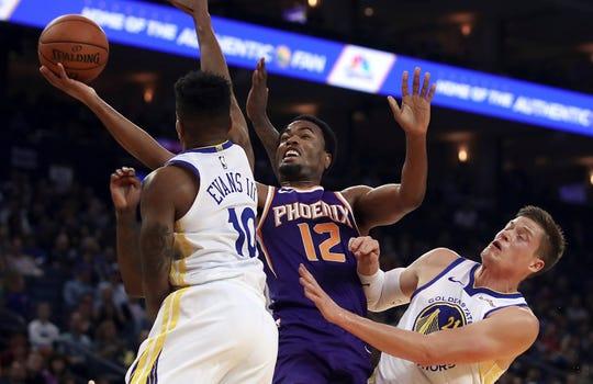 Phoenix Suns' TJ Warren (12) lays up a shot between Golden State Warriors' Jacob Evans, left, and Jonas Jerebko (21) during the first half of a preseason NBA basketball game Monday, Oct. 8, 2018, in Oakland, Calif. (AP Photo/Ben Margot)