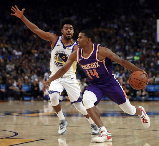Phoenix Suns' De'Anthony Melton, right, drives the ball against Golden State Warriors' Quinn Cook (4) during the first half of a preseason NBA basketball game Monday, Oct. 8, 2018, in Oakland, Calif.