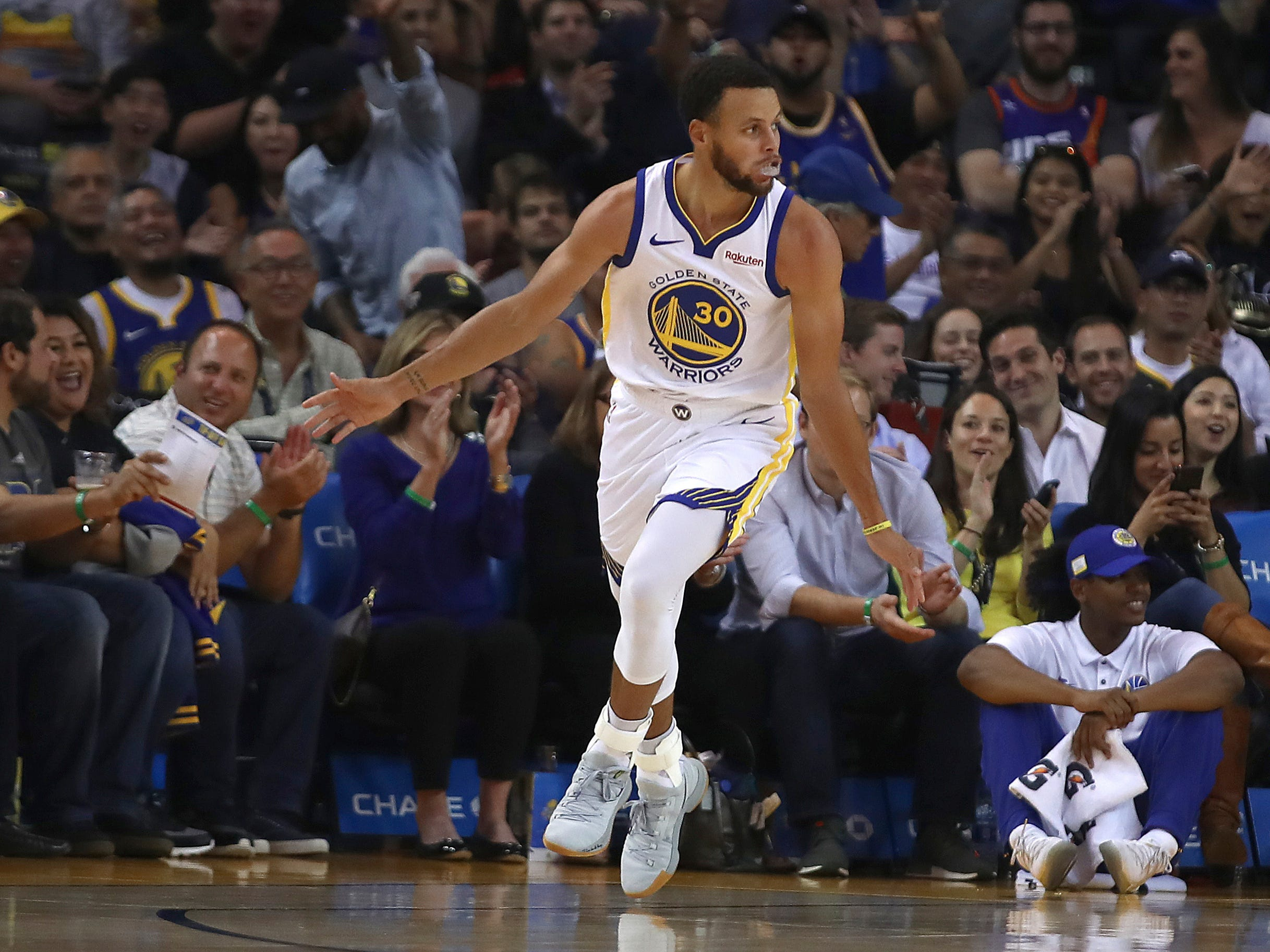 Golden State Warriors' Stephen Curry celebrates after scoring against the Phoenix Suns during the first half of a preseason NBA basketball game Monday, Oct. 8, 2018, in Oakland, Calif.