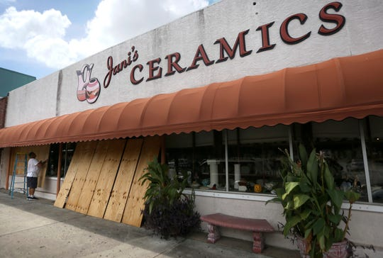 Bobby Smith cubre las ventanas de Jani's Ceramics en Panama City, Florida, el lunes 8 de octubre de 2018, en preparación para la llegada del huracán Michael.