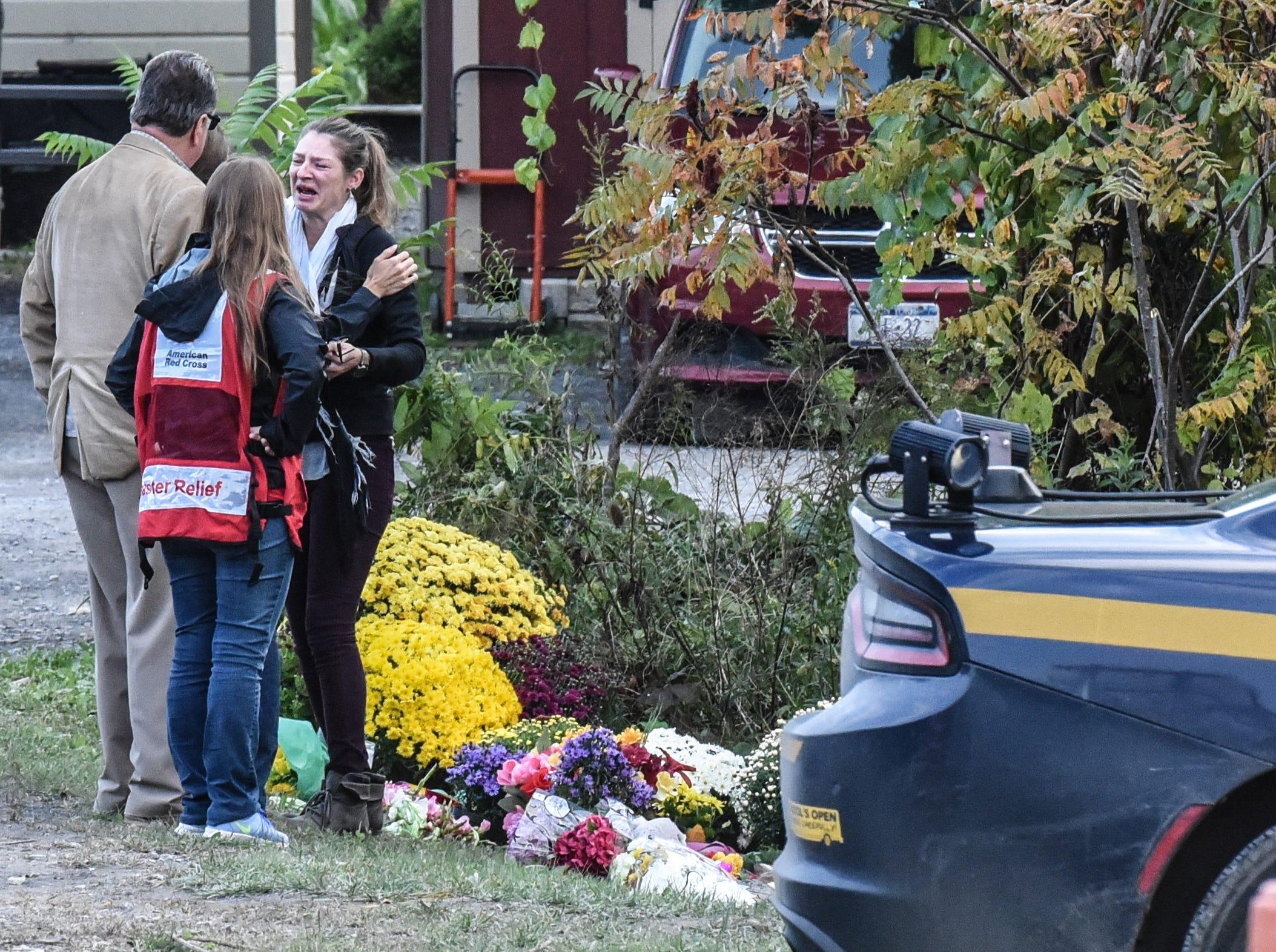 La gente se lamenta en el lugar del fatal accidente de limusina mientras los autos se acercan al sitio del accidente el 8 de octubre de 2018 en Schoharie, Nueva York. 20 personas murieron en el accidente, incluido el conductor de la limusina, 17 pasajeros y dos peatones.