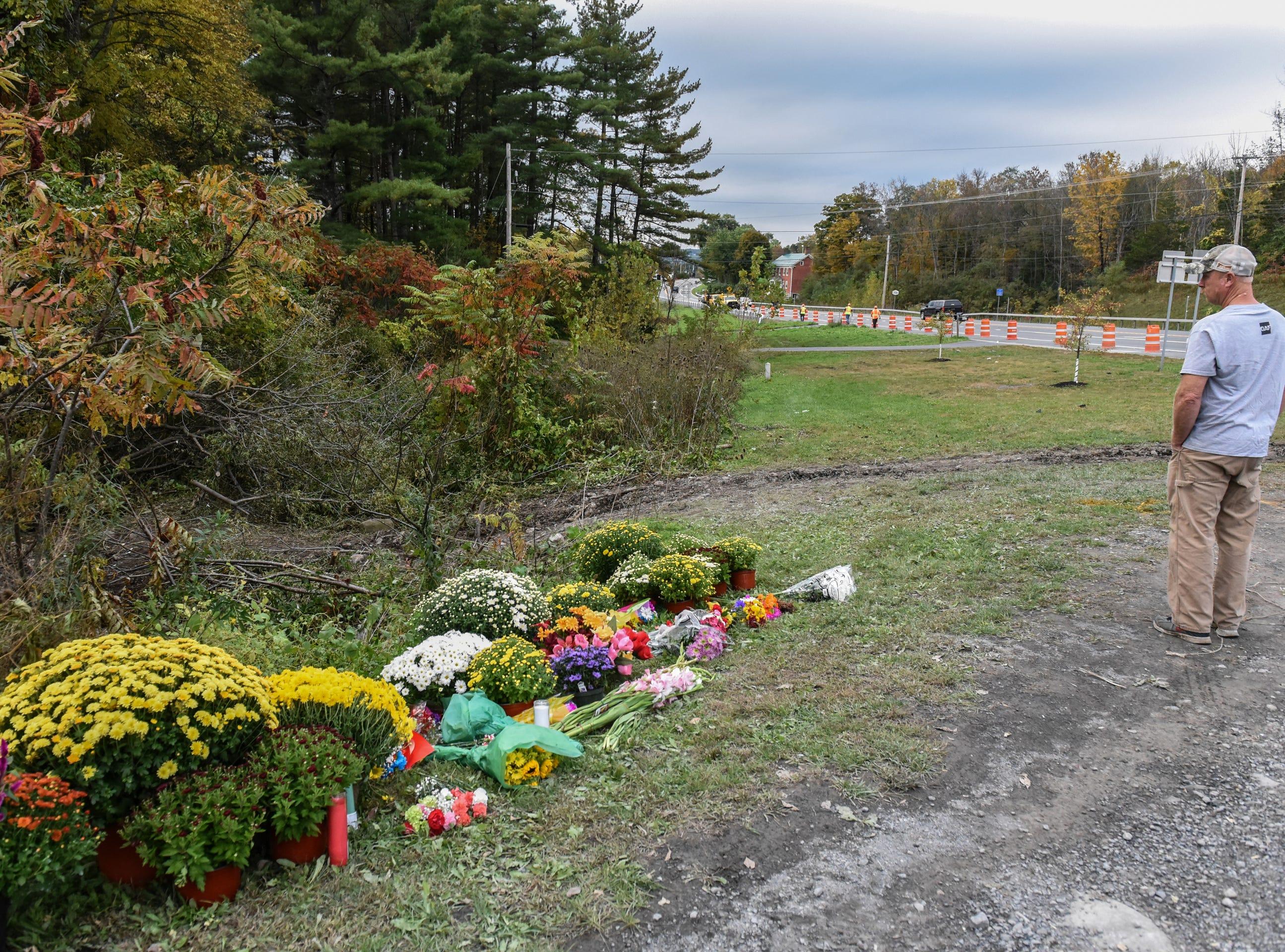 Un doliente mira el sitio del fatal accidente de limusina el 8 de octubre de 2018 en Schoharie, Nueva York. 20 personas murieron en el accidente, incluido el conductor de la limusina, 17 pasajeros y dos peatones. Las huellas de la limusina se pueden ver en el otro lado de las flores.