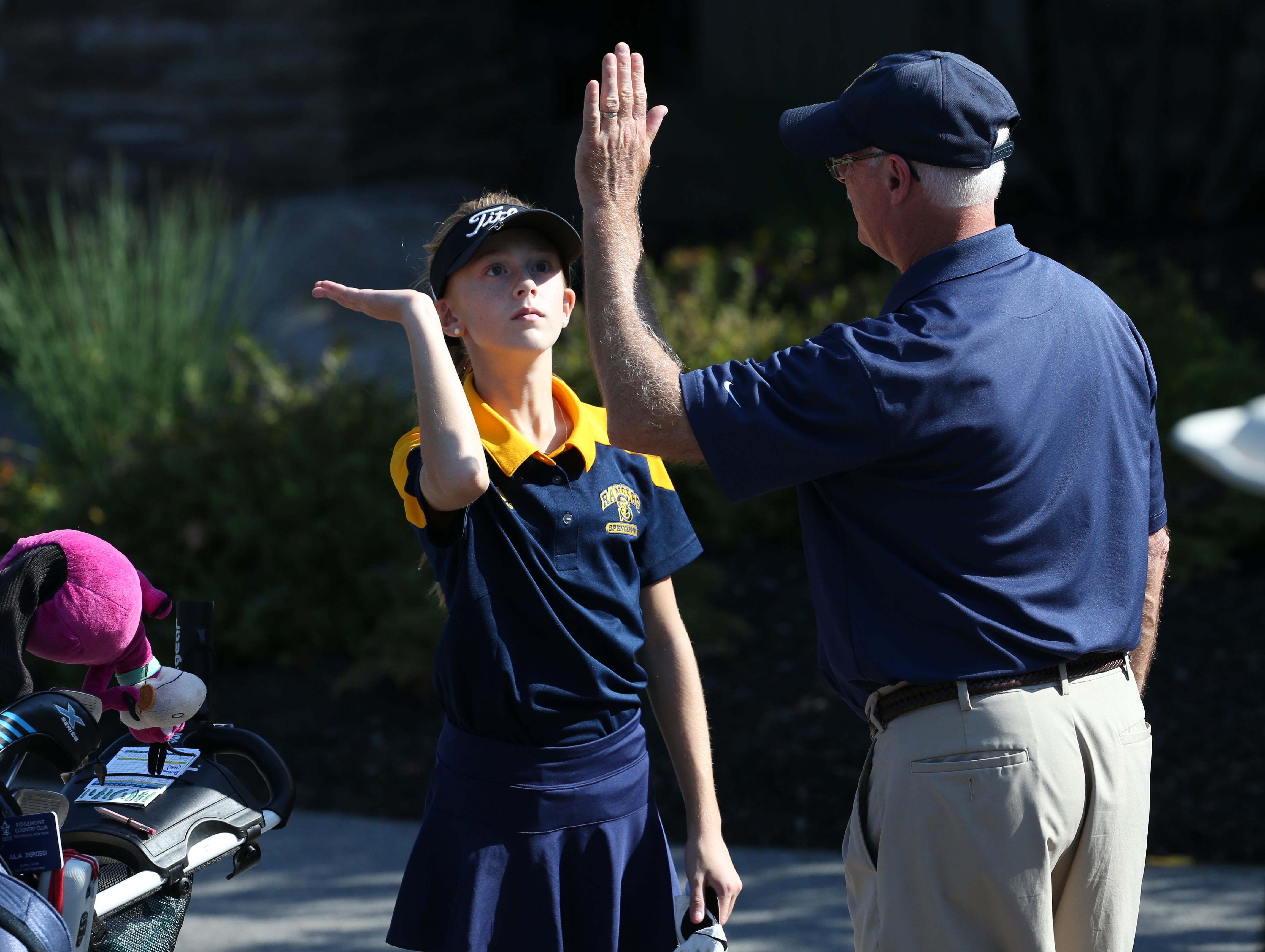 Julia Zigrossi high- fives her coach Mark Moon at the Section V girls golf championship at Deerfield Country Club.