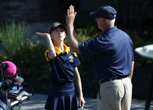 Julia Zigrossi high- fives Spencerport coach Mark Moon at the Section V girls golf championship at Deerfield Country Club.