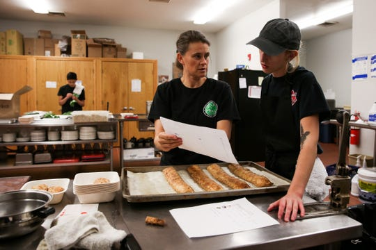 Lianne Wieweck (left) goes over a list of meals with Keila Smothers (right) at the South Salem Senior Center on Monday, Oct. 8, 2018. The prepared meal service changes their menu weekly.