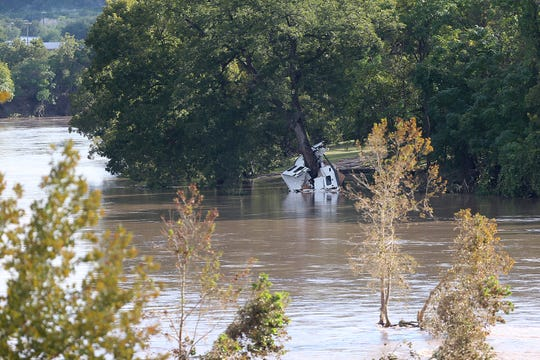 Pieces of an RV is wrapped around a tree in flood waters near the South Llano River Bridge Monday, Oct. 8, 2018 in Junction, Texas after heavy rainfall caused flooding and washed away a nearby RV park.