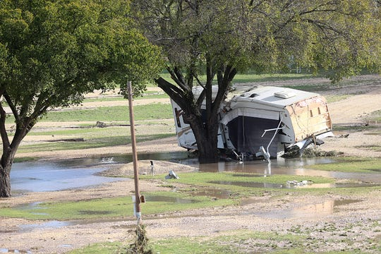 Pieces of an RV rests against a tree in flood waters near the South Llano River Bridge Monday, Oct. 8, 2018 in Junction, Texas after heavy rainfall caused flooding and washed away a nearby RV park.