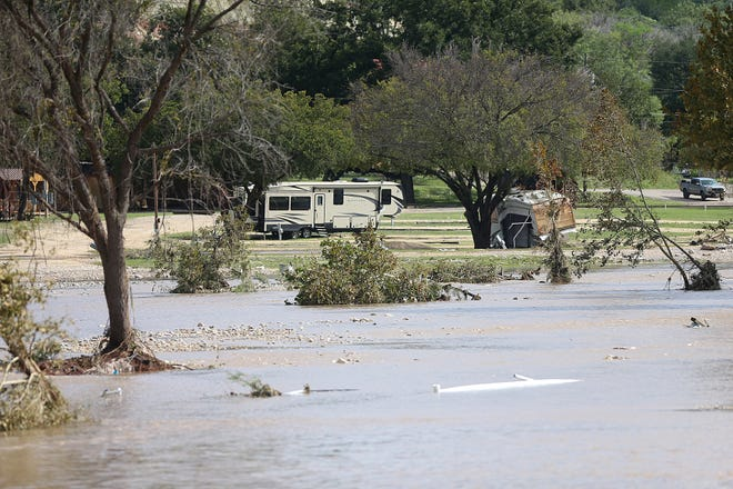 Damaged and overturned RVs are scattered near the South Llano River Bridge Monday, Oct. 8, 2018 in Junction, Texas after heavy rainfall caused flooding and washed away a nearby RV park.