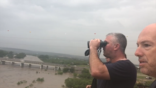 People in Junction watch and yell encouragement as a man fights South Llano River floodwaters Monday, Oct. 8, 2018, in Junction, Texas. The man, who had shed his clothes because they were dragging him down, was lifted to safety via helicopter.