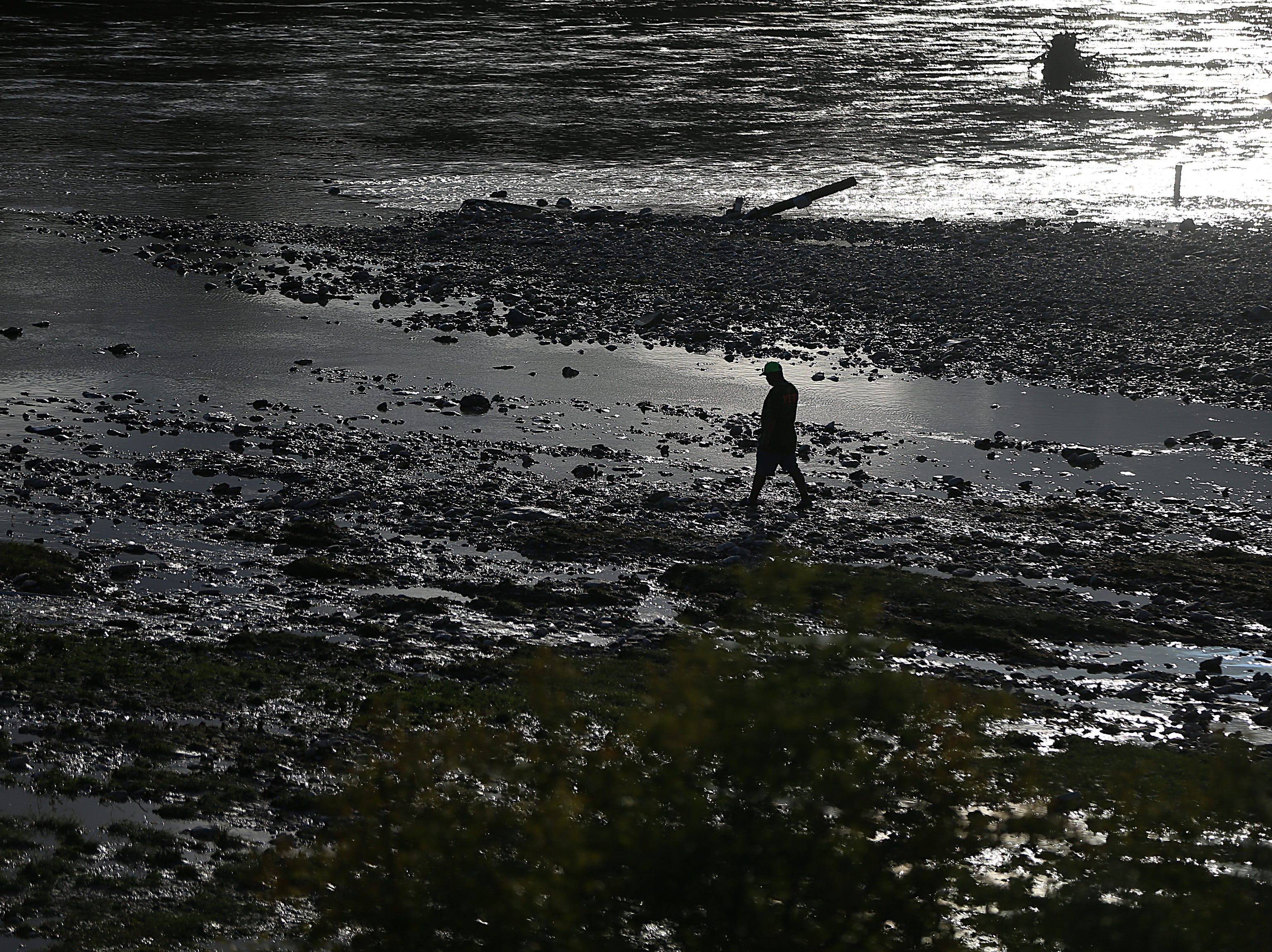 A man walks in the riverbed of the South Llano River after flood waters subside Monday, Oct. 8, 2018 in Junction, Texas. Heavy rainfall caused flooding and washed away a nearby RV park.